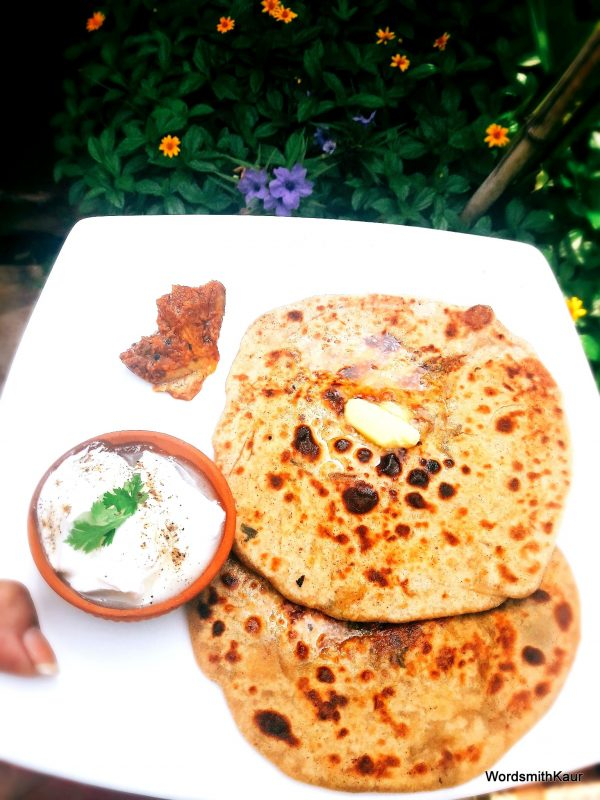 Remove the Aloo ka Paratha with raw potatoes from fire and serve hot with a dollop of butter, pickle and a bowl of fresh yoghurt.